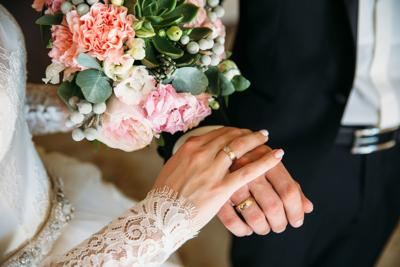 Closeup groom and bride are holding hands at wedding day ang show rings. Concept of love family