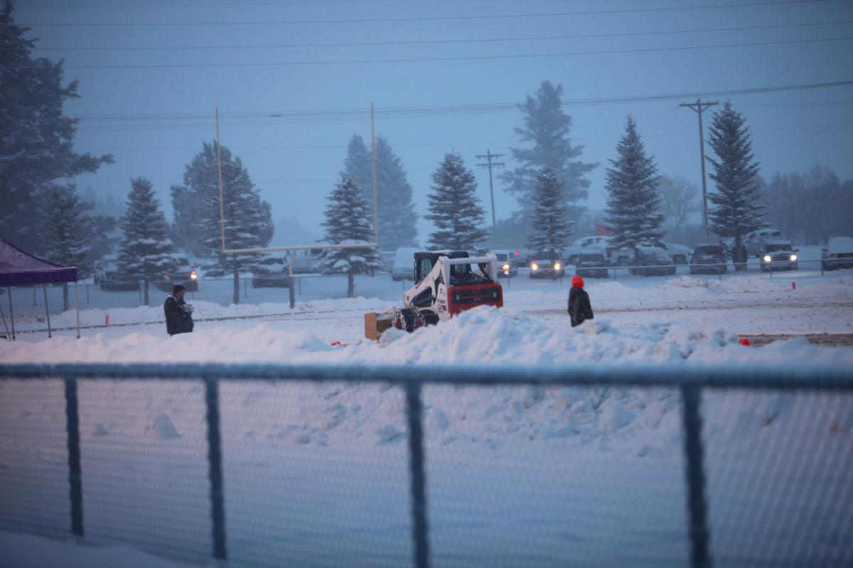 A skid steer loader attempts to clear the snowy North Fremont field at halftime. Skid steer operators tried to rid the field of snow throughout the game during timeouts and other breaks in play.