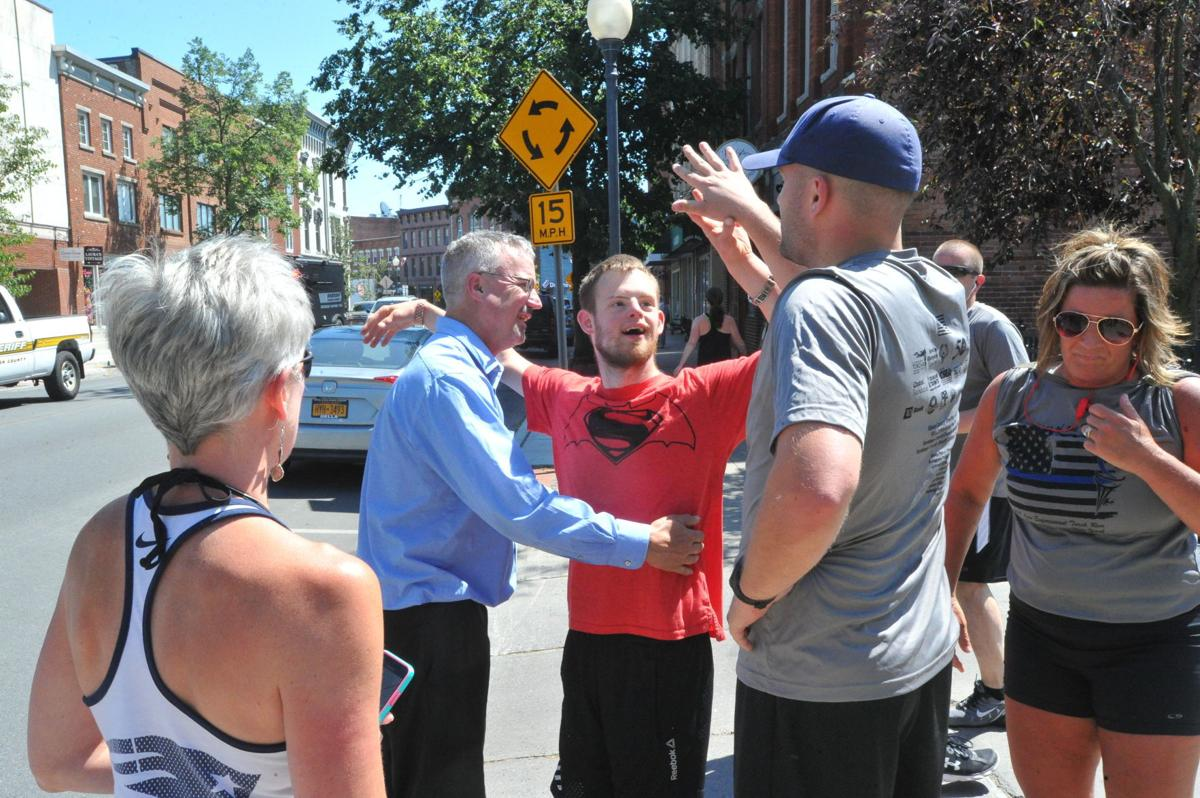 Maxwell high-fives runners at finish