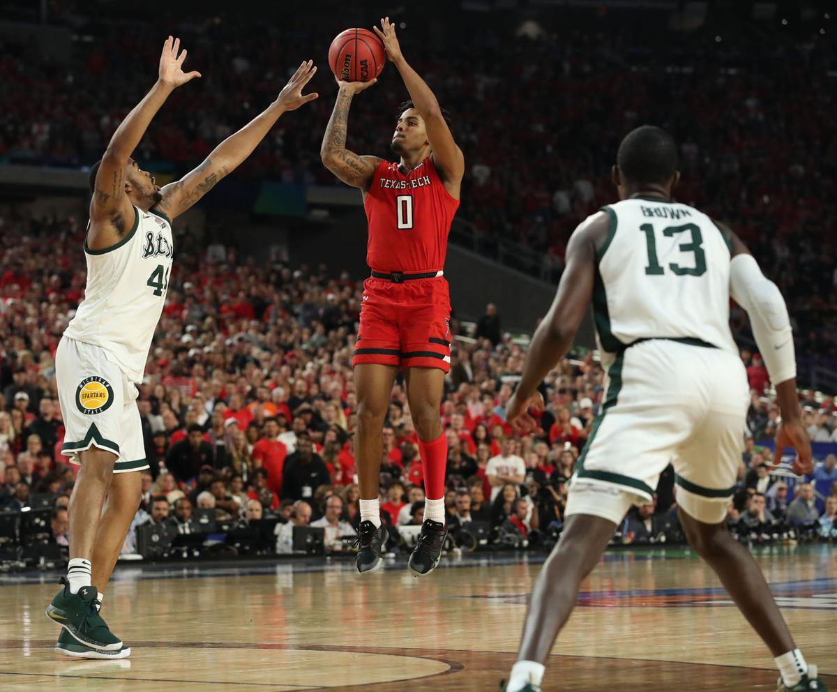 Texas Tech's Kyler Edwards (0) shoots against Michigan State's Nick Ward (44) and Gabe Brown (13) during the first half in a semifinal of the NCAA Tournament Final Four on Saturday, April 6, 2019, at U.S. Bank Stadium in Minneapolis.