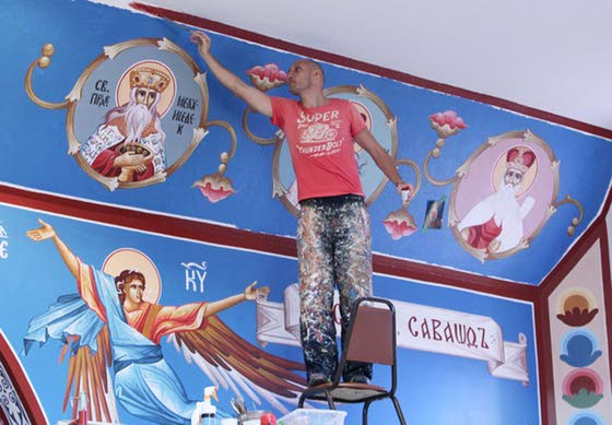 Iconographer paints spiritual images on walls of church to inspire faithful