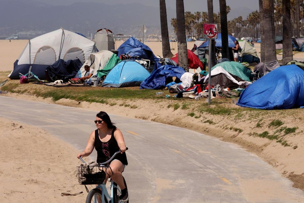 A bicyclist rides past several homeless tents along the bike path in Venice on April 16, 2021.