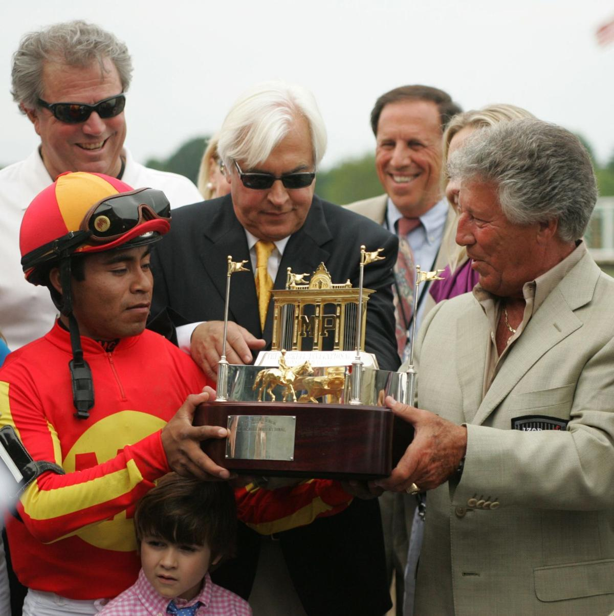 Looking at Lucky' Jockey, Martin Garcia, left, smiles while holding the 2010 Haskell trophy with trainer Bob Baffert, and race car legend, Mario Andretti, right. The 2010, $1,000,000 IZOD Haskell at Monmouth Park in Oceanport, Sunday, August 1, 2010.