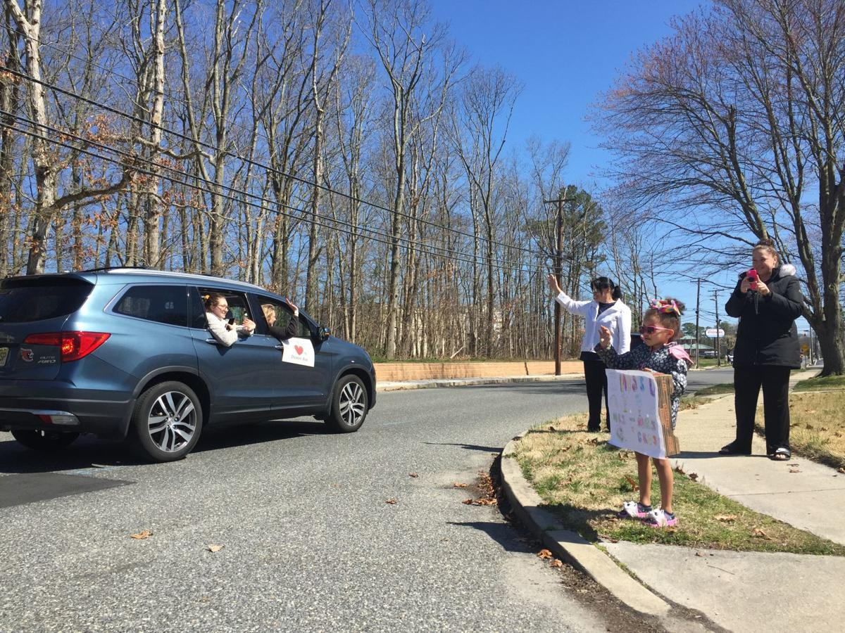 Somers Point students and parents wave to Dawes Avenue School staff as they parade in their cars around the city Thursday, March 26, 2020.