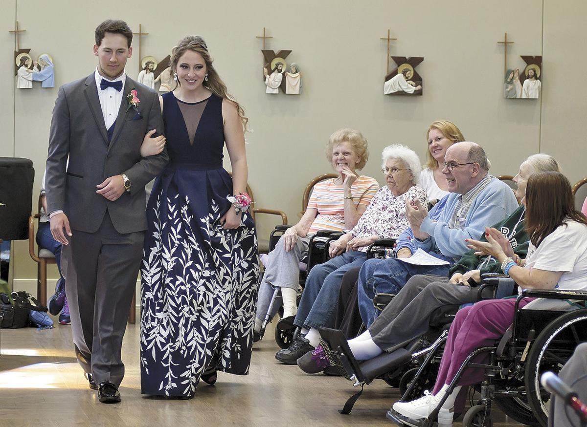 Students take a prom march through Cerenity Senior Care Center