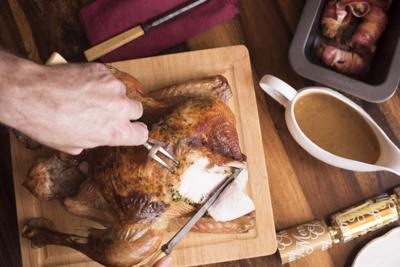 Man carving the Christmas roast turkey for dinner