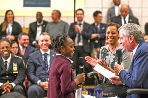 <p>Amaryllis Greene, 9, has a few questions for Mayor de Blasio on the subways, homelessness and the NYPD at a Nov. 13 town hall meeting in Jamaica as Councilwoman Adrienne Adams and the crowd at August Martin High School look on.</p>