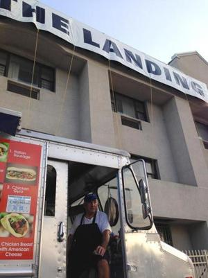 <p>Christo Vangelatos, left, sits in his food truck parked outside The Landing, a new shelter for families that used to be the Clarion Hotel.</p>
