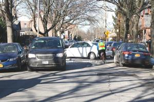 <p>It was a tight squeeze on Alderton Street in Rego Park on Tuesday, as a cyclist tries to navigate a double-parked minivan, parked cars and a motorist backing into his driveway. The DOT is entertaining the idea of making the roadway a one-way street, an idea that some community leaders are not very fond of.</p>