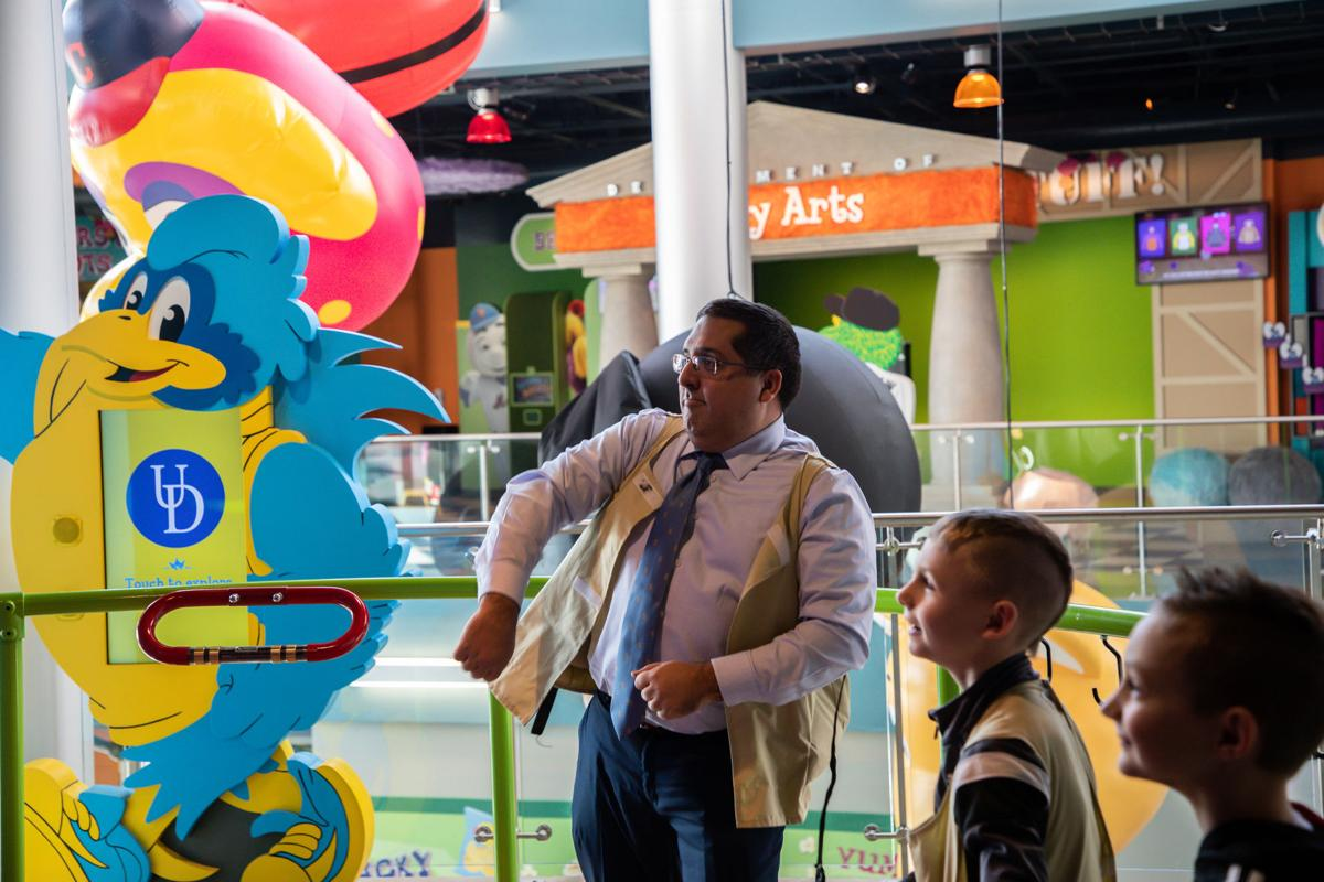 Orestes Hernandez, executive director of the Mascot Hall of Fame in Whiting, dances with visitors Carson Planer, 7, and Jason Keck, 8.