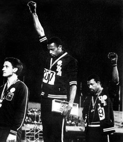 Athletes Tommie Smith (center) and John Carlos (rigt) raise their gloved fists in the Black Power salute to express their opposition to racism in the United States during the U.S. national anthem, after receiving their medals Oct. 16, 1968 for first and third place in the men's 200m event at the Mexico Olympic Games. At left is Peter Norman of Australia, who took second place.