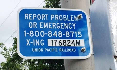 Railroad crossing signs for reporting problems or emergencies