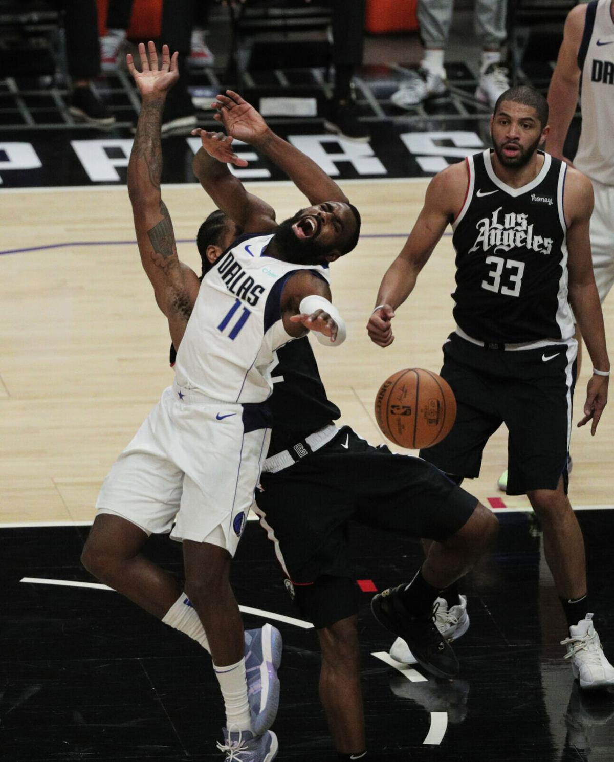 Dallas Mavericks forward Tim Hardaway Jr. and Los Angeles Clippers forward Kawhi Leonard collide going for a loose ball in game seven of the first round of the NBA Playoffs at Staples Center on Sunday, June 6, 2021 in Los Angeles, California.