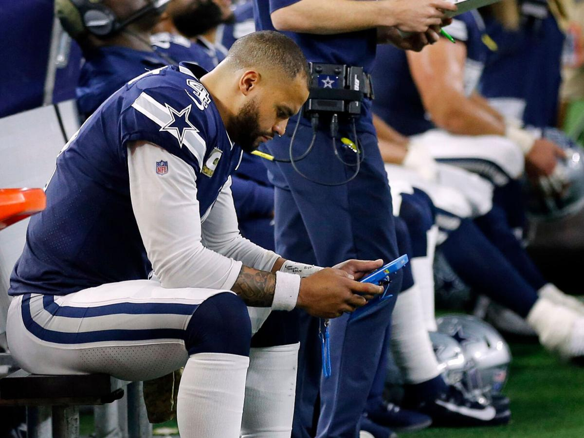 Dallas Cowboys quarterback Dak Prescott (4) looks at a tablet on the bench in the fourth quarter against the Minnesota Vikings at AT&T Stadium in Arlington, Texas, on November 10, 2019.