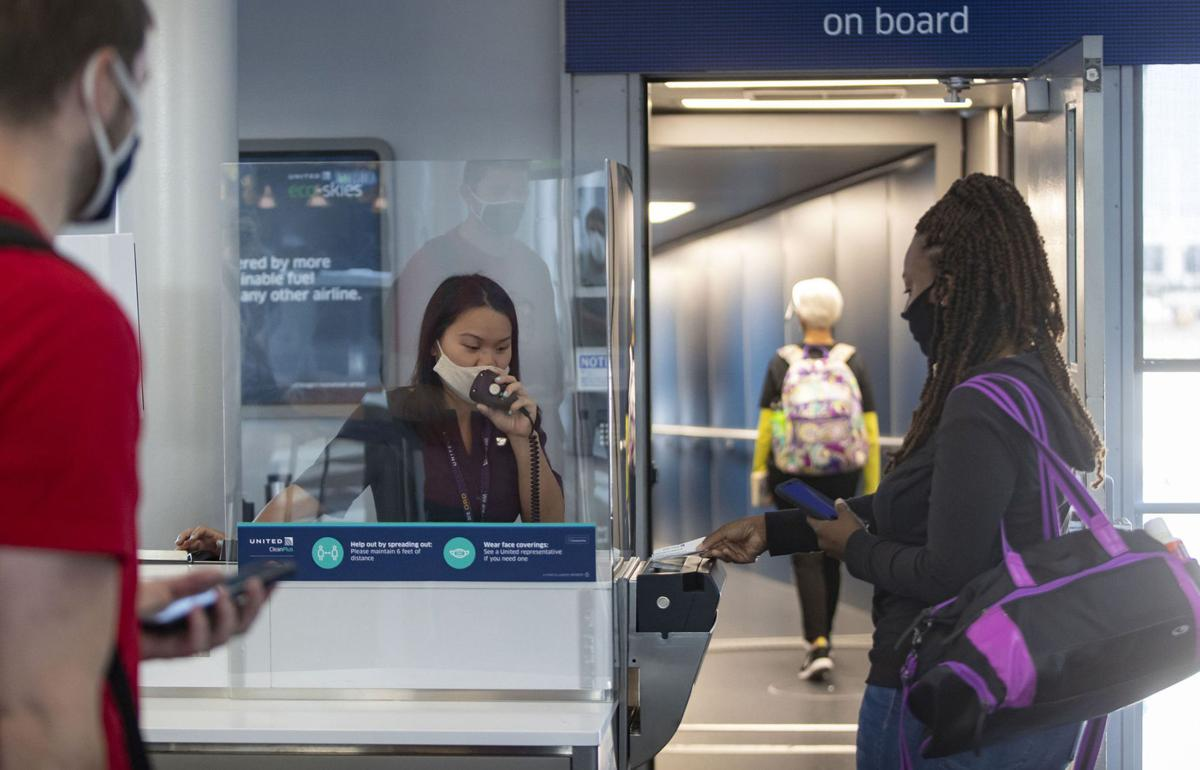 United Airlines gate agent Emma Watt helps passengers scan their boarding passes for a flight to San Francisco at O'Hare International Airport on June 18, 2020.