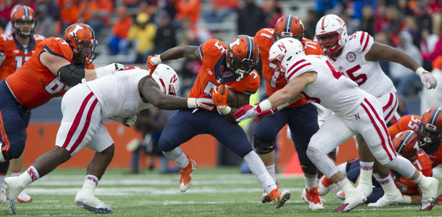 Maliek Collins (7) and linebacker Chris Weber (49) combine to stop Illinois running back Ke'Shawn Vaughn