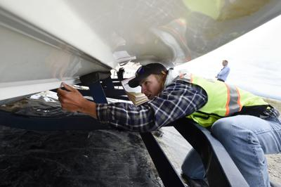 Watercraft inspector Ryan Dorvall gets a closer look at the hull of a boat