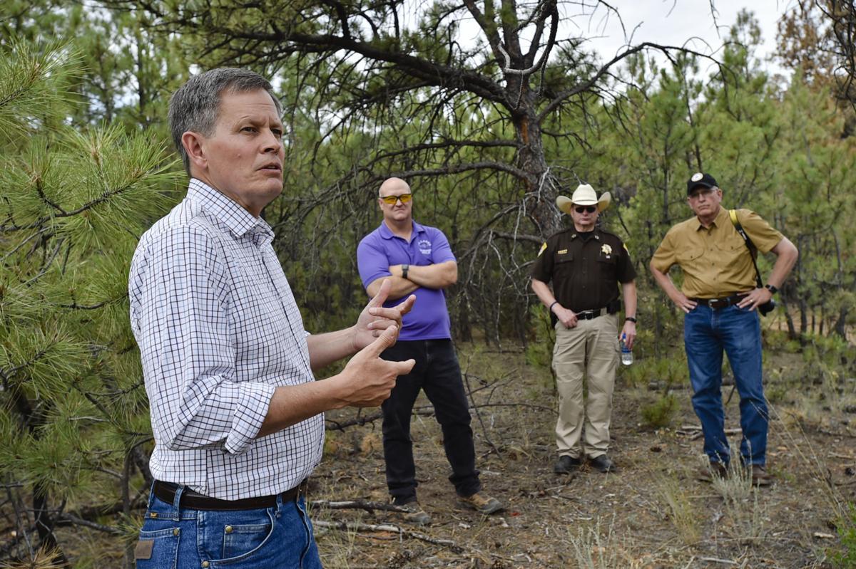 Sen. Steve Daines, left, talks about wildfire legislation