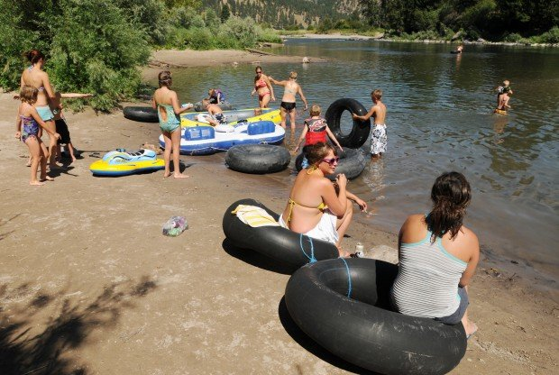 A group of people and assortment of tubes sit on the Clark Fork River bank.