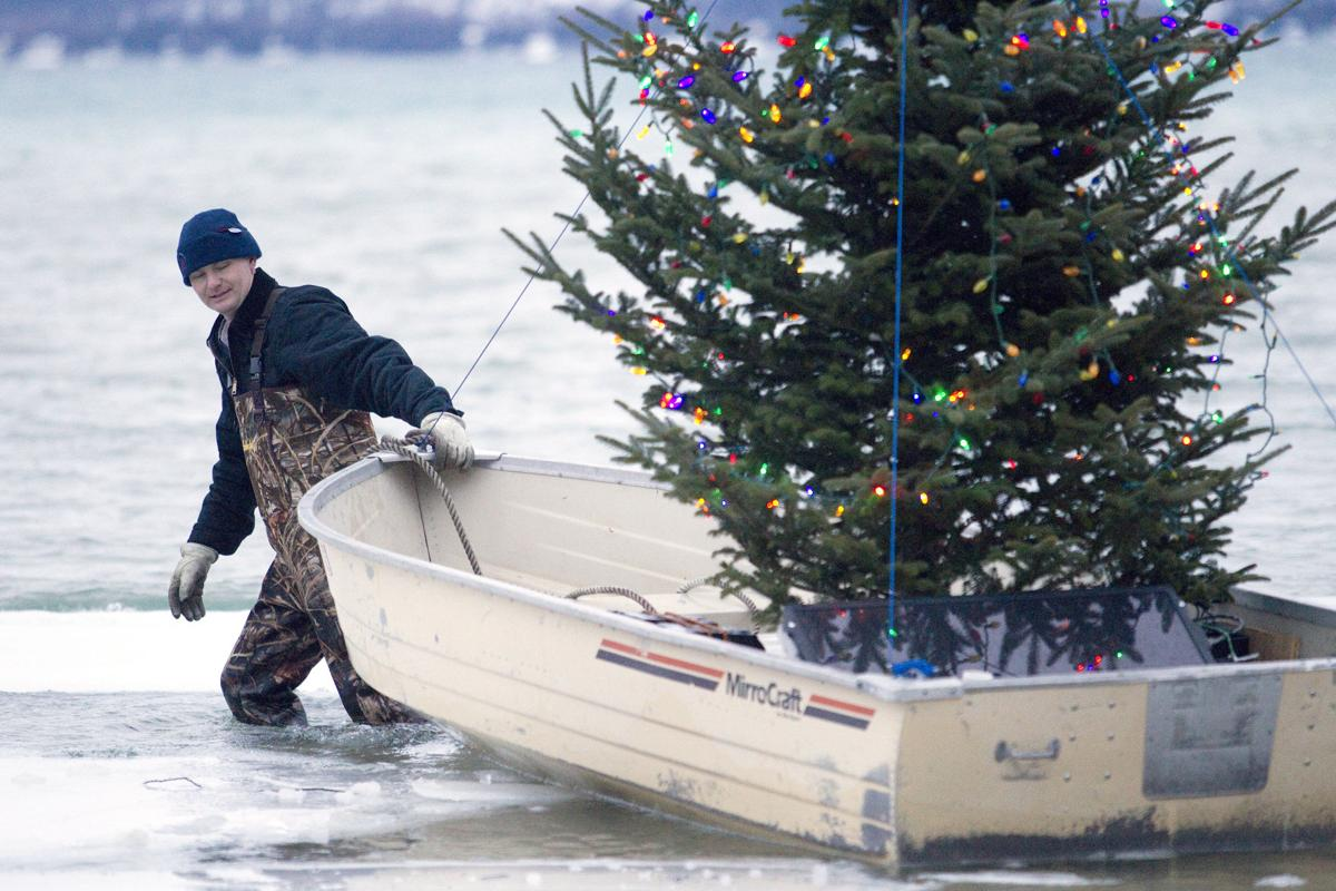 frank siepker wades out into the chilly winter water on big glen lake to retrieve his floating christmas tree for a battery change