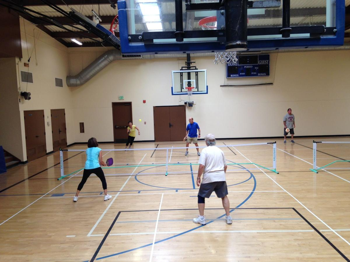 Photo shows an example of seniors playing Pickleball in an indoor gym.