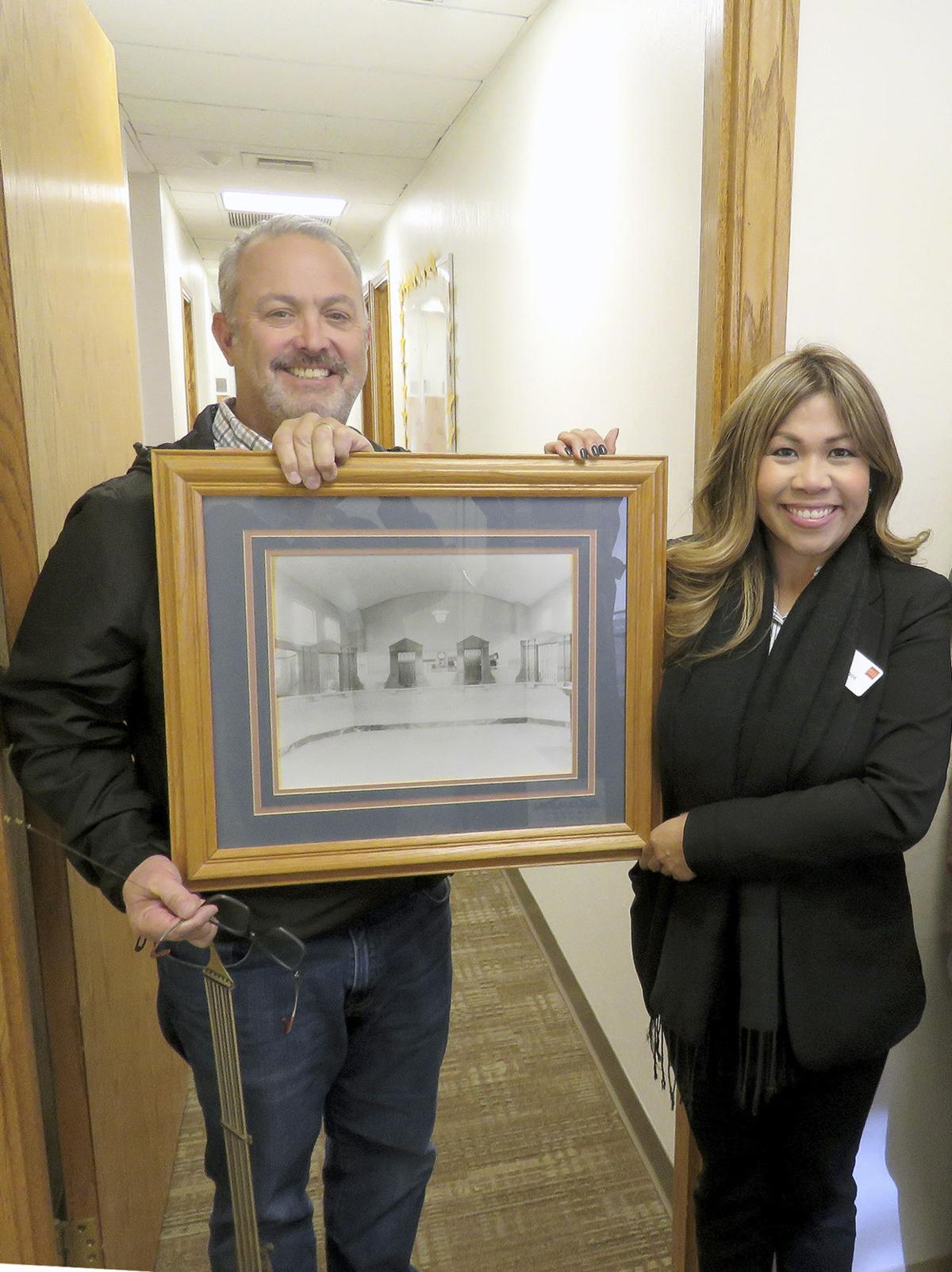 San Gorgonio Pass Historical Society President Sean Balingit, with Wells Fargo branch manager Catherine Ramos, hold a framed picture of the interior of the Bank of Beaumont