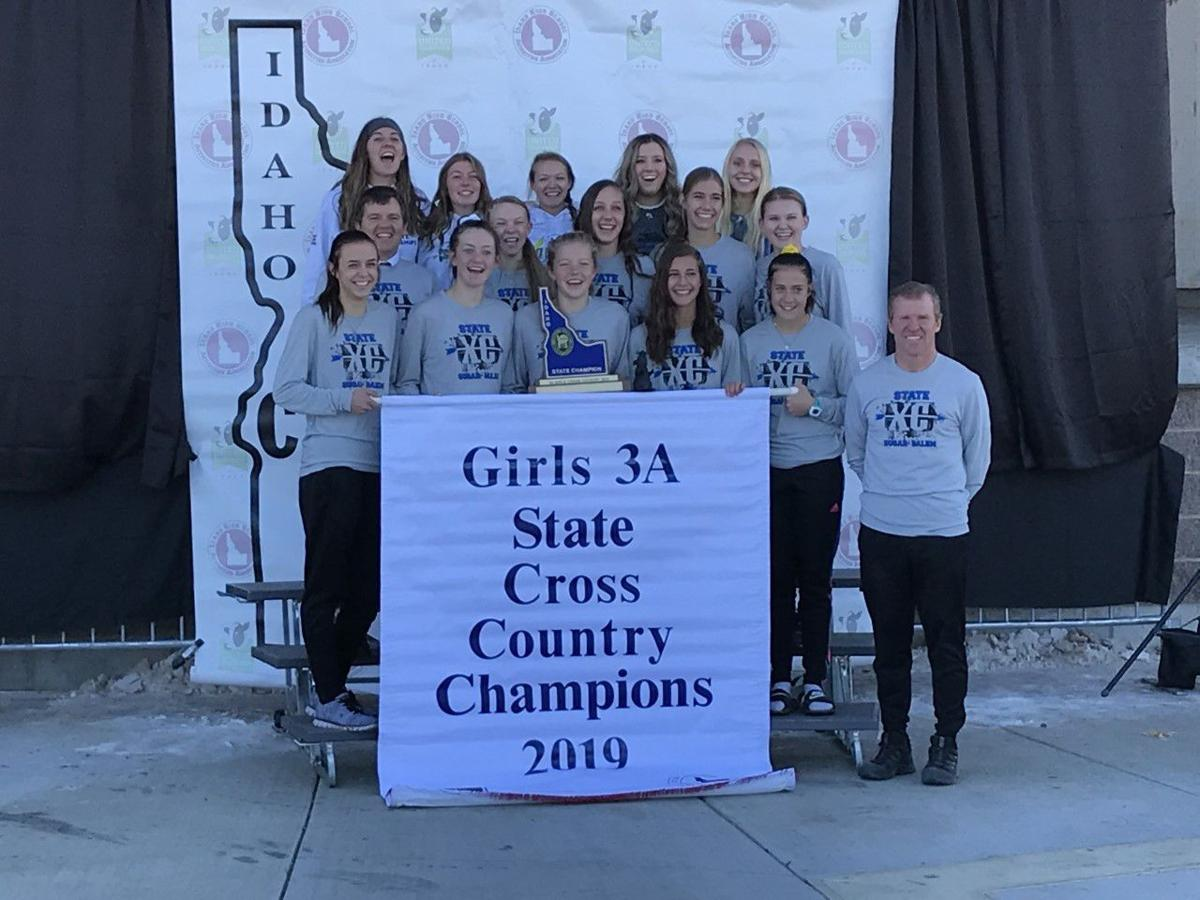 Sugar-Salem's girls cross country team poses for a photo with their banner and trophy.