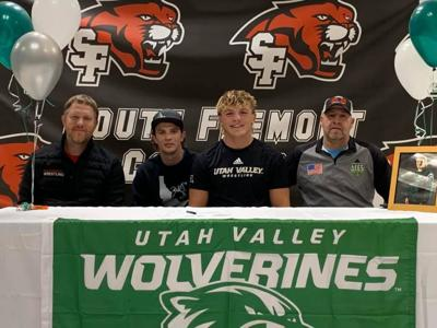 South Fremont's Sawyer Hobbs poses for a photo with his coaches after signing to wrestle at UVU.