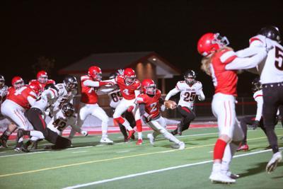 Madison quarterback Easton Cordero cuts away from defenders.