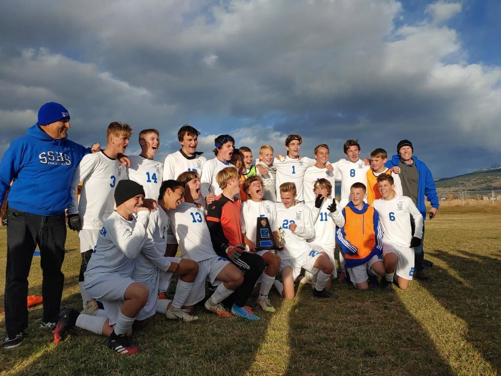 Sugar-Salem's boys soccer pose for a photo with their fourth-straight district championship trophy.