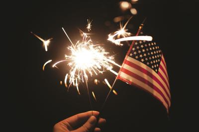 Hand holding lit sparkler with American Flag