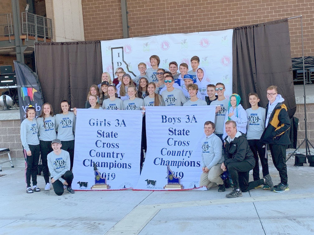 Sugar-Salem girls and boys cross country teams pose for a photo with their championship banners and trophies.