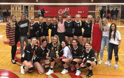 Madison's volleyball team poses for a photo with their title trophy.