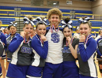 Brayton Pope poses for a photo with some of his cheer teammates after taking first in the district cheer competition this winter.