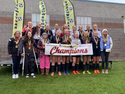 Madison's U17 Girls team gathers for a photo with their Yellowstone Cup trophy and banner.