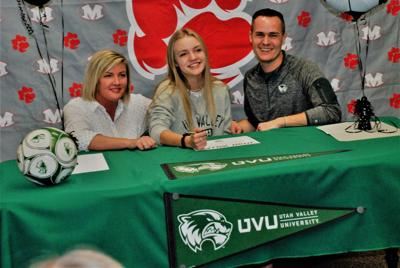 Madison's Annalise Brunson signs her letter of intent to play soccer at Utah Valley University surrounded by her parents, Jeff and Mary Brunson.