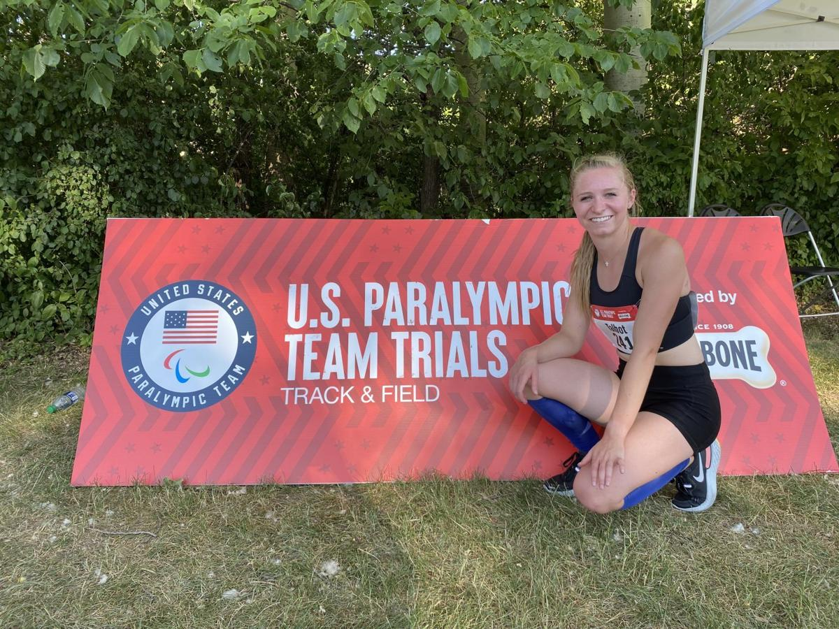 Taylor Talbot stands next to a sign at the US Paralympic trials in Golden Valley, Minnesota.