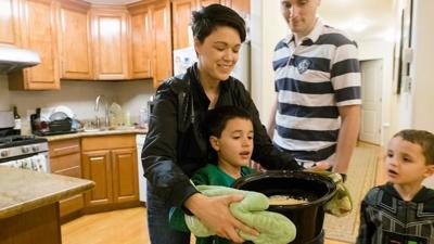 Parents help their children cook dinner. The new Children and Youth program helps children set goals to learn new skills.