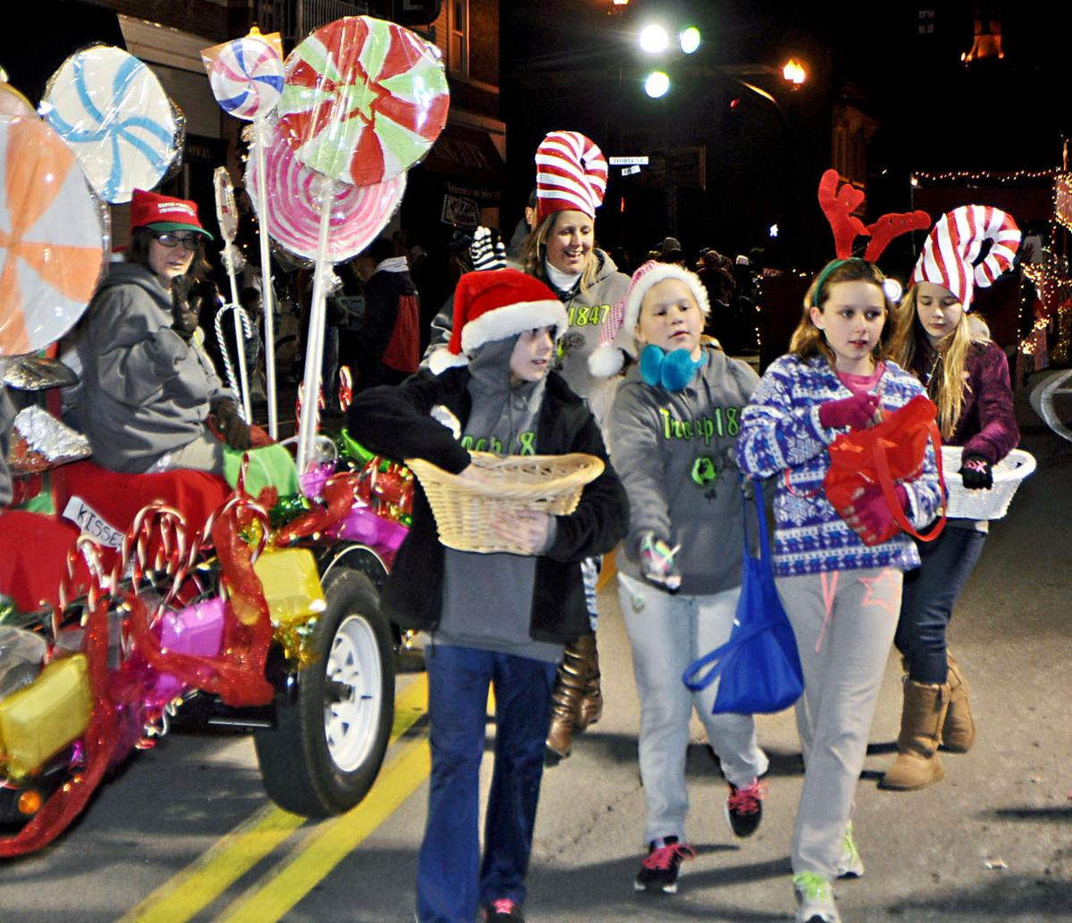 1847 toss lollipops friday night as they walk down main street next to their lollipop float in richmonds night of twinkling lights christmas parade