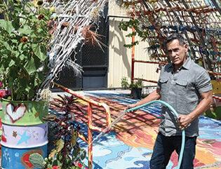 Roger Montoya watering MAE garden