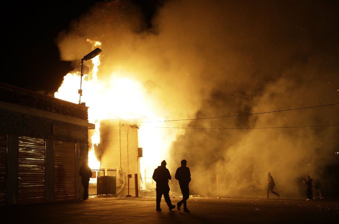 People walk away from a storage facility on fire after the announcement of the grand jury decision Monday, Nov. 24, 2014, in Ferguson, Missouri.