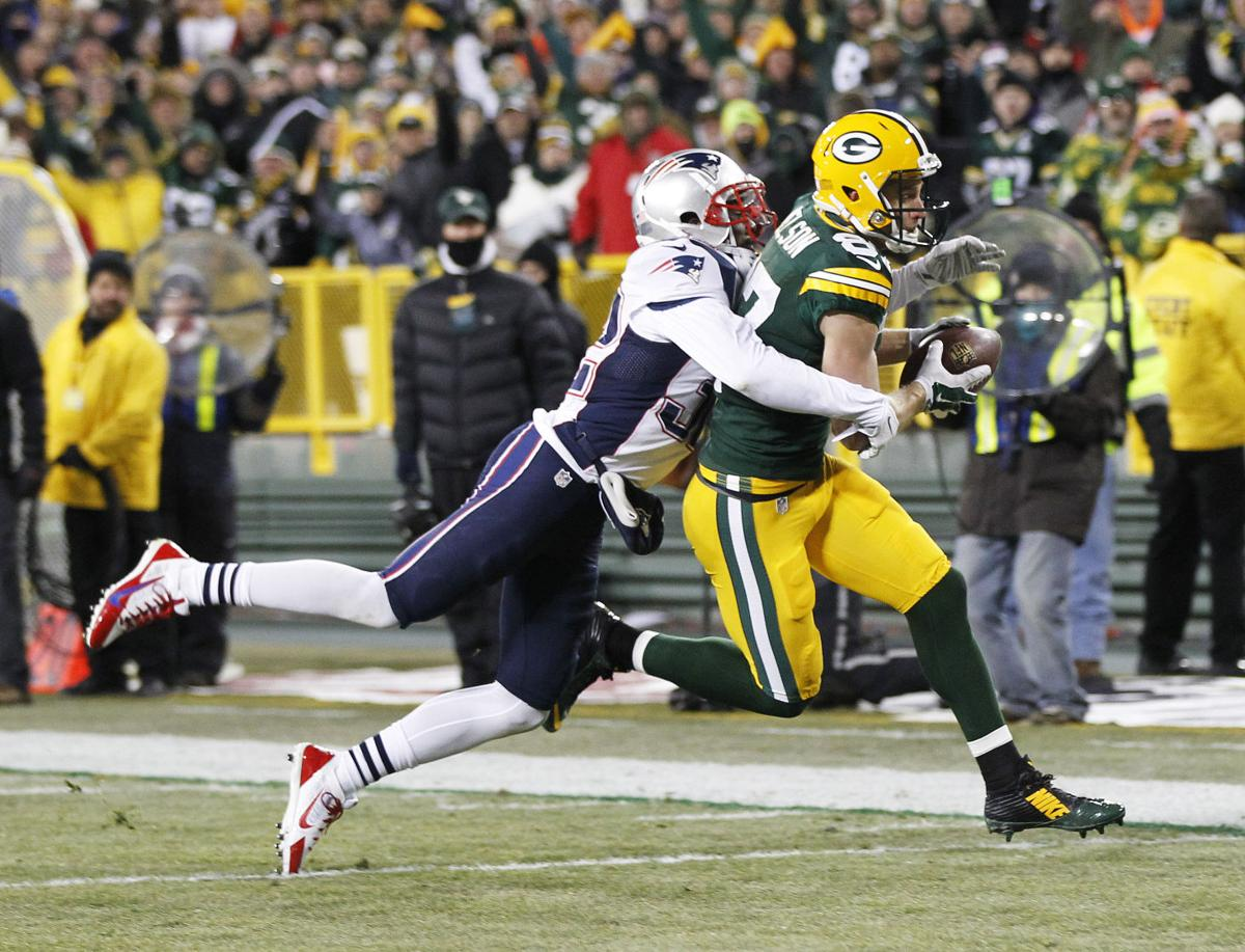 Green Bay Packers' Jordy Nelson scores a touchdown in front of New England Patriots' Devin McCourty after a catch during the first half.