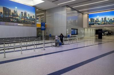 An airport worker stands in a nearly empty TSA Pre queue on Saturday, March 14, 2020 at Terminal 7 of Los Angeles International Airport in Los Angeles, Calif. LAX Ambassador Nahid Naiem said crowds of travelers were down about 40 percent.