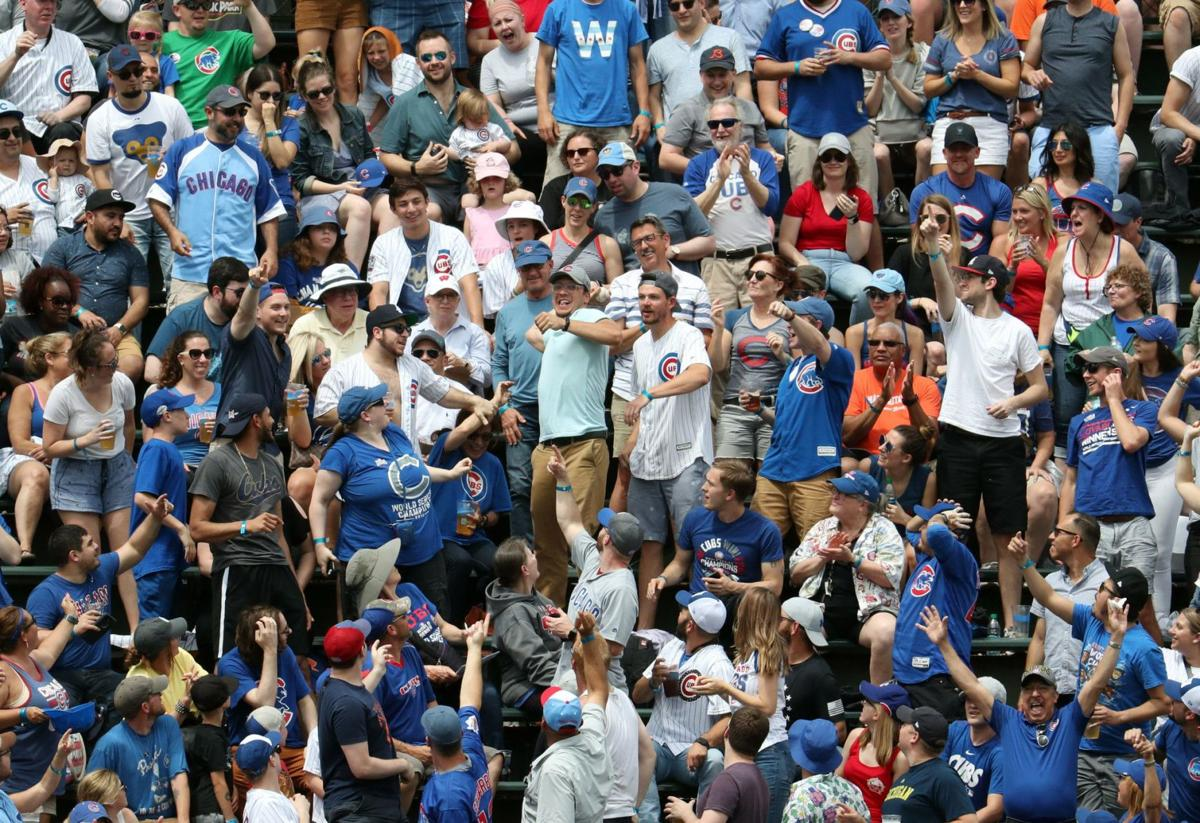 A Cubs fan in the Wrigley Field bleachers throws back a home run by Mets catcher Tomas Nido on June 23, 2019.