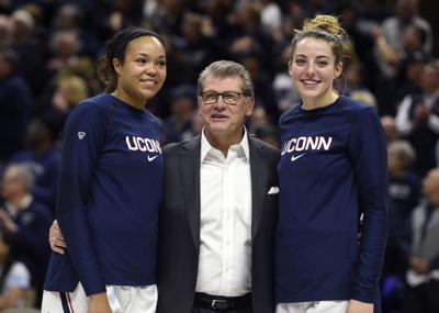Connecticut head coach Geno Auriemma is flanked by forwards Napheesa Collier, left, and Katie Lou Samuelson on Senior Day at Gampel Pavilion in Storrs, Conn., on March 2, 2019.