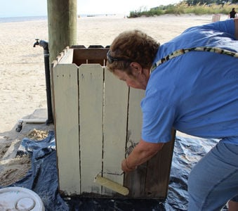 Joan Coleman paints trash can.