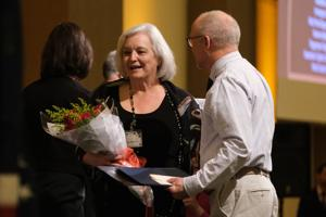 <p>Dr. Mary Krueger holds flowers after being presented the Athena Award Saturday night.</p>