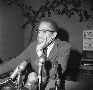"""<p>In this May 22, 1964, file photo, civil rights leader Malcolm X speaks during a press conference in Chicago. """"Who Killed Malcolm X?"""" currently streaming on Netflix dives into questions surrounding his 1965 assassination and allegations of a botched investigation. (AP Photo/Edward Kitch, File)</p>"""