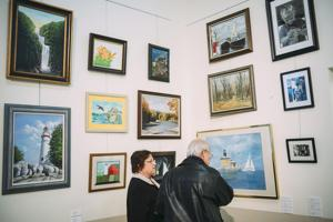 <p>File. Clara Marks (left) and husband Ed Marks (right), of Perrysburg, look at art on display for the first annual 50+ Shades of Grey senior art exhibit.</p>