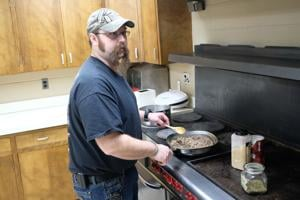 <p>Steve Stachoviak at the stove, browning sausage for his Italian Stuffed Shells.</p>
